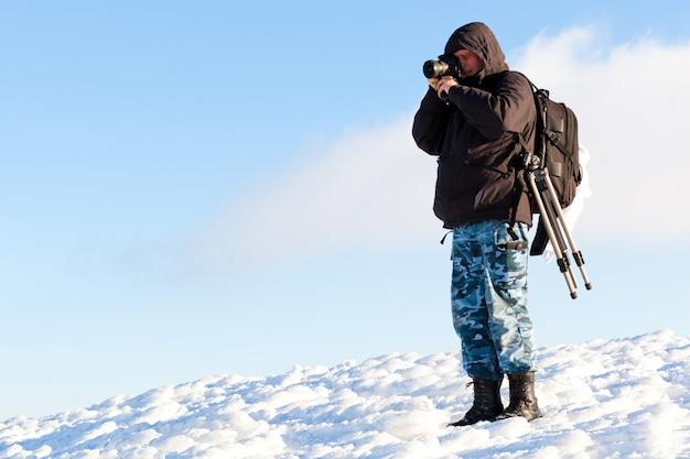 겨울 옷을 입고 햇빛에 사진을 만드는 젊은 남자 사진 작가