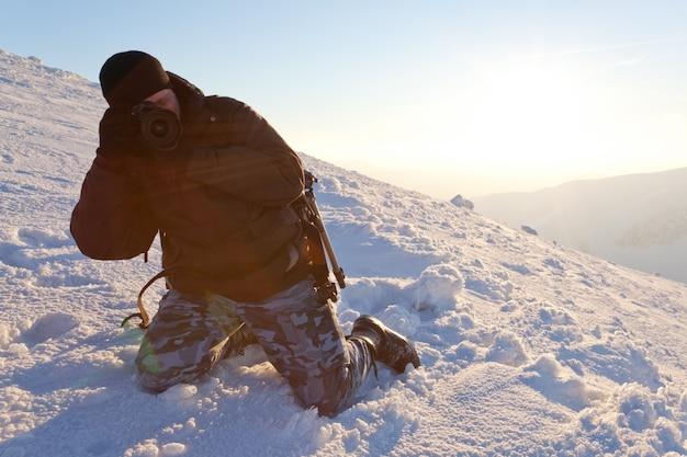 Фотограф молодого человека в одежде зимы стоя и делая фото в солнечном свете