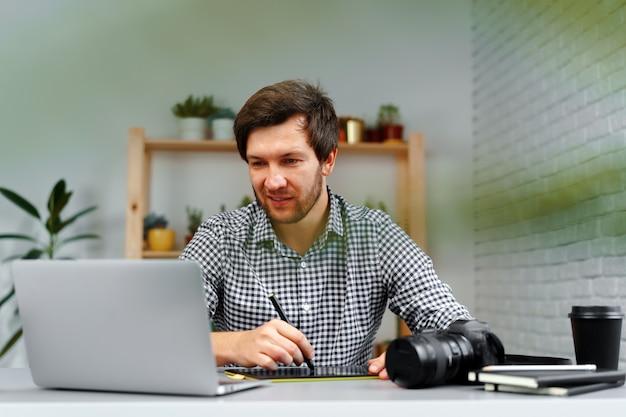 젊은 남자 사진 작가 테이블에 앉아서 가정에서 작동