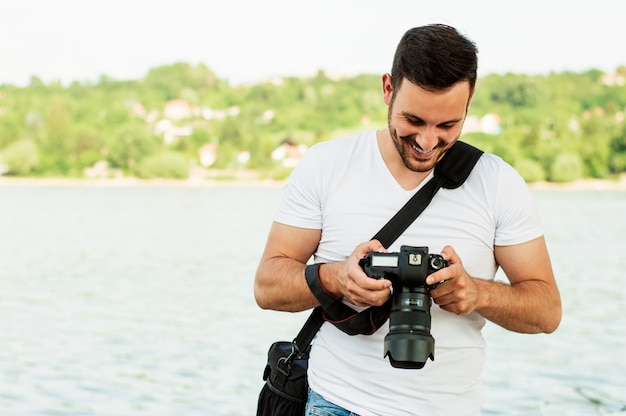 Young man photographer takes pictures with dslr camera