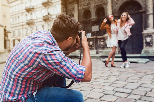 Young man photographer taking pictures, taking photos with digital camera to her friends