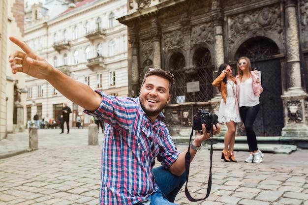Молодой человек фотограф снимает, фотографирует с цифровой камерой своим друзьям