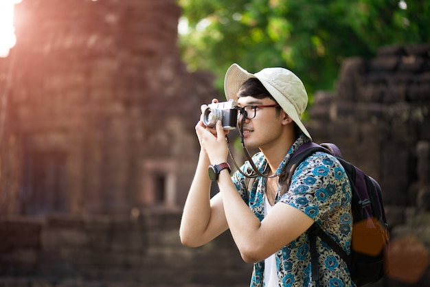 Young man photographer traveler with backpack taking photo