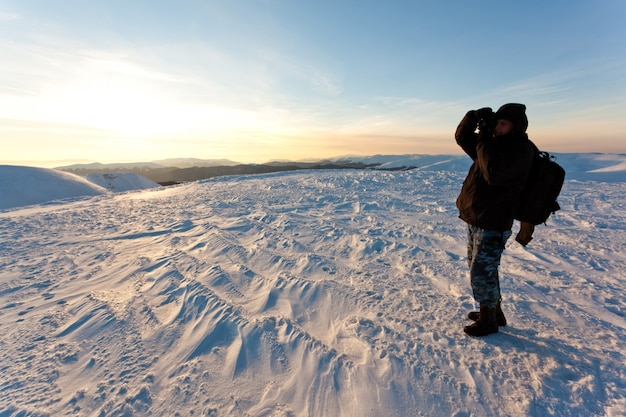 Young man photographer in winter clothing standing and making photo with camera in sunlight with white snow background