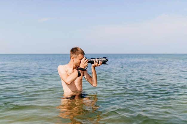 Young man photographer with camera stands waist-deep in sea and takes pictures