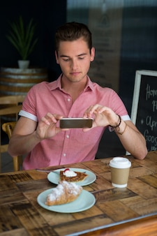 Young man photographing food on table in coffee house