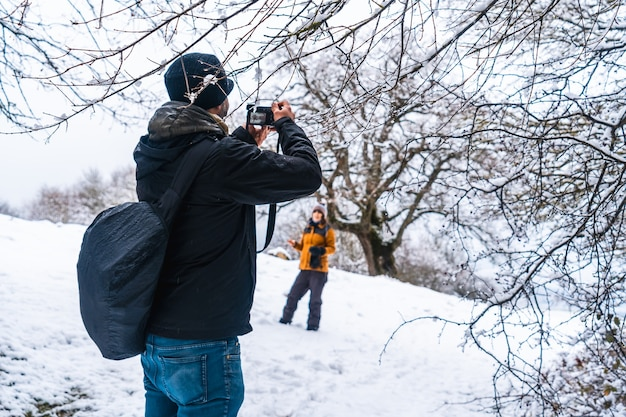 A young man photographing a girl in the snow. snow in the town of opakua near vitoria