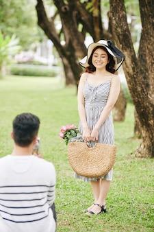 新鮮なバラのバスケットと都市公園でポーズをとってガールフレンドを撮影する若い男