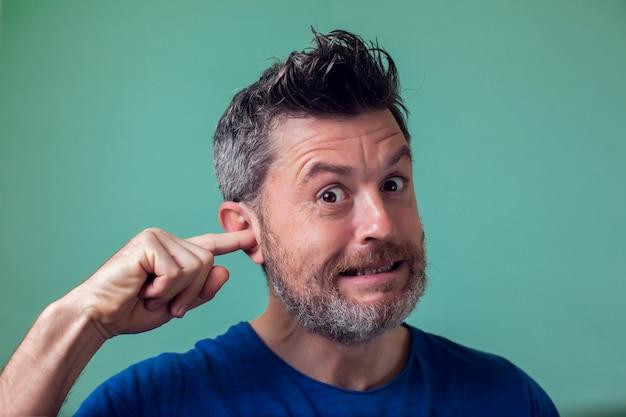 Молодой человек, выбирая его ухо с его пальцем- люди, здравоохранение и эмоции