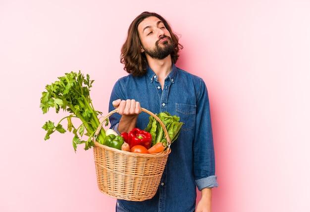 Молодой человек, собирающий экологически чистые овощи в своем огороде, мечтает о достижении целей и задач