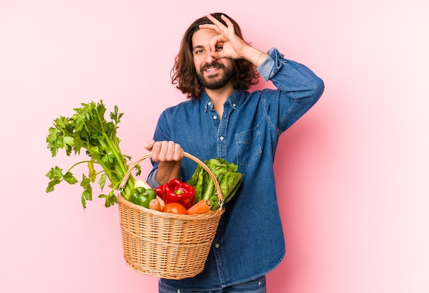 分離された彼の庭から有機野菜を選ぶ若い男は興奮してokのしぐさを目に保持しています。