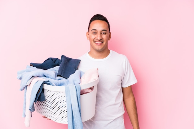 Young man picking up dirty clothes isolated happy, smiling and cheerful