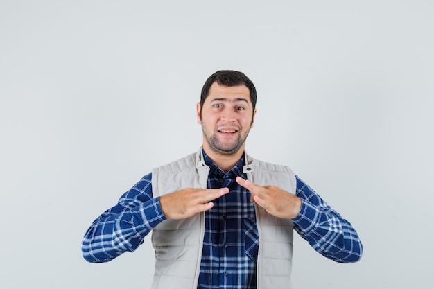 셔츠, 민소매 재킷에 그의 칼라를 꼬집고 지루해 보이는 젊은 남자. 전면보기.