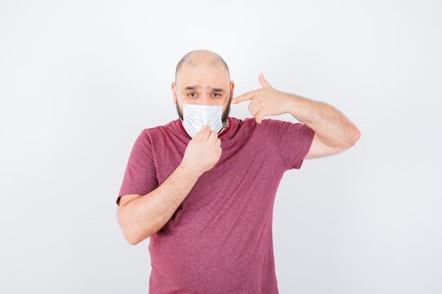 젊은 남자는 분홍색 티셔츠를 입고 마스크를 가리키면서 마스크를 꼬집습니다.
