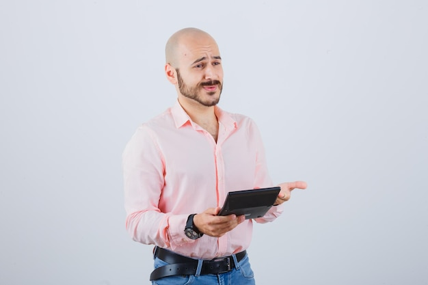 Young man in pink shirt,jeans holding calculator while talking with someone , front view.