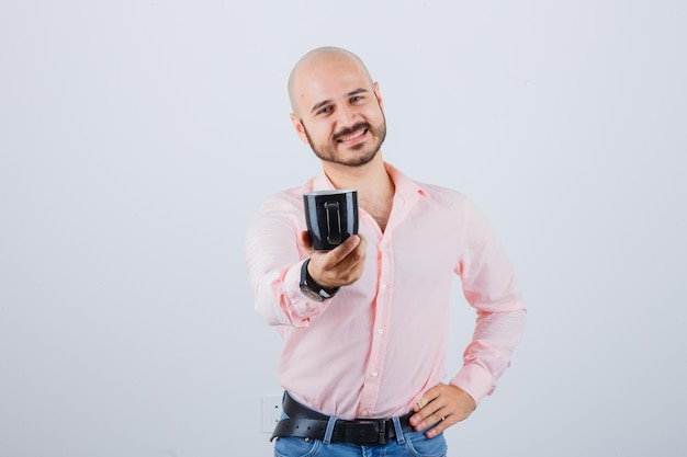 Young man in pink shirt,jeans holding cup while smiling , front view.