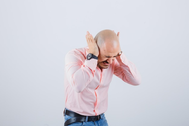 Young man in pink shirt,jeans holding hands on ears while bending forward and looking crazy , front view.