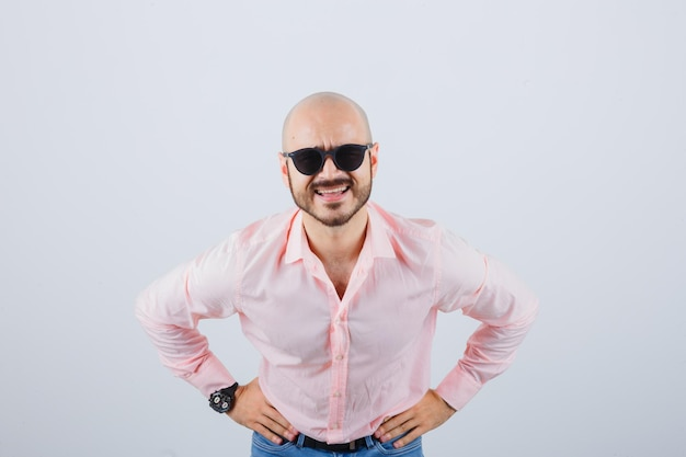 Young man in pink shirt,jeans,sunglasses asking something with hands on waist and looking curious , front view.