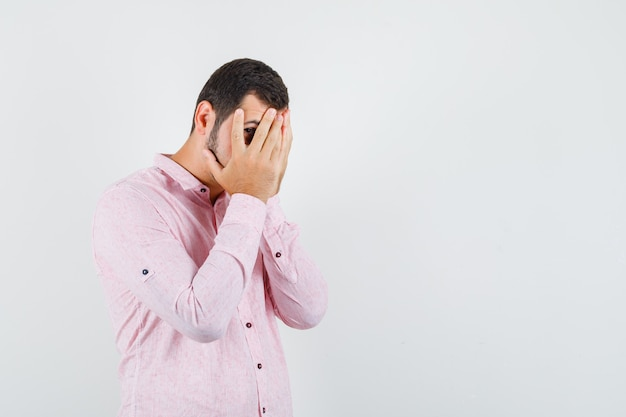 Young man in pink shirt looking through fingers and looking scared