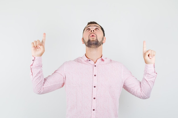 Giovane uomo in camicia rosa rivolto verso l'alto e guardando grato