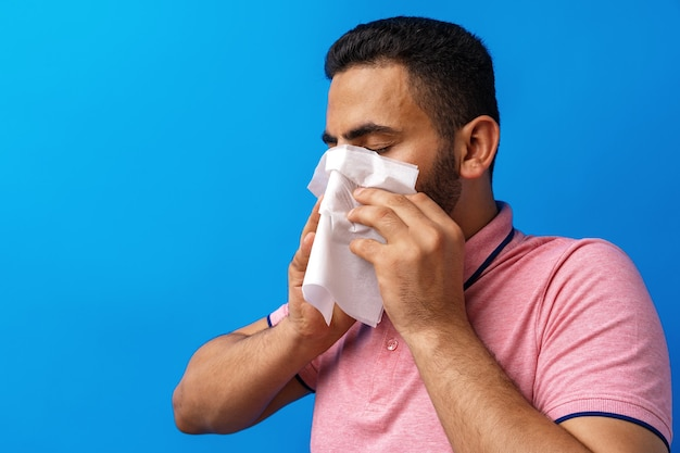 Young man in pink shirt with allergy or cold blowing his nose in a tissue against blue background