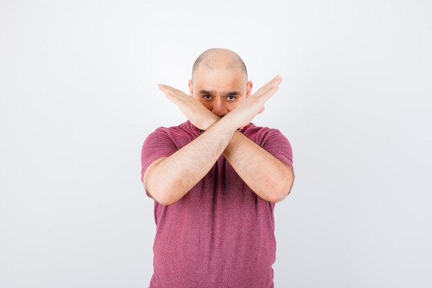 Giovane in maglietta rosa che mostra restrizione o gesto x e sembra serio, vista frontale.