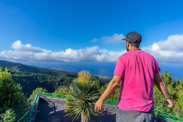 A young man in a pink t-shirt on top of the mountain at the viewpoint of the cubo de la galga