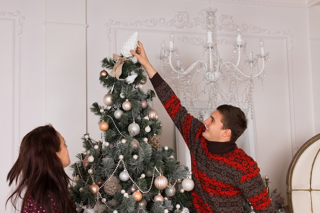 彼のガールフレンドが横から見ているように伸びるクリスマスツリーの上に飾りを置く若い男