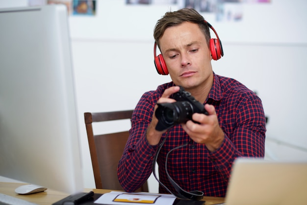 Young man in plaid shirt and headphones sitting at desk, holding digital camera and looking at photos