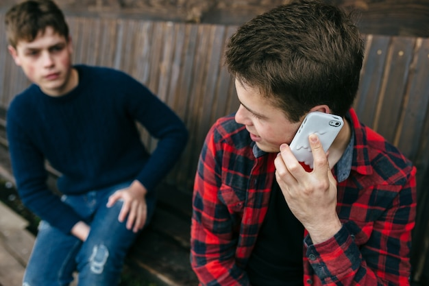 Giovane uomo in una camicia a quadri parlando sullo smartphone