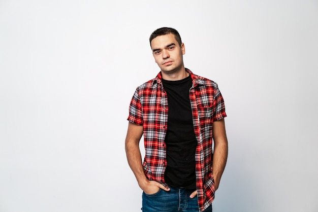 Young man in a plaid shirt with hands in his pockets looks straight into the camera