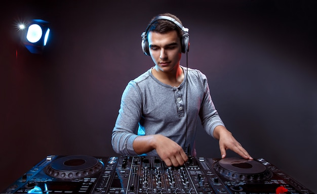 Young man play music on a dj's mixer at studio