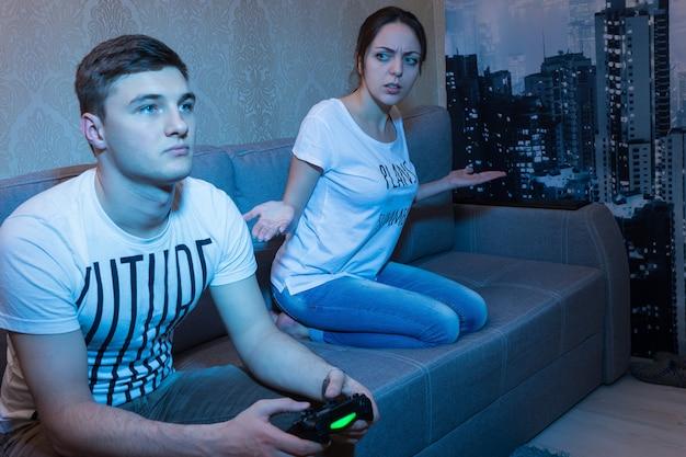 완전히 무시하고 있는 좌절한 아내나 여자친구가 지켜보는 비디오 게임을 하는 젊은 남자
