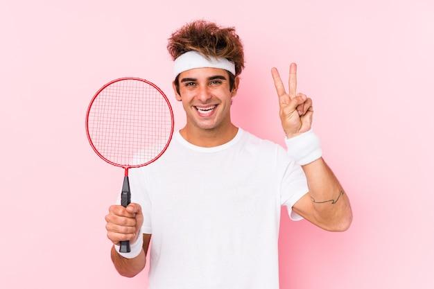 Молодой человек, играя в бадминтон изолировал, показывая номер два пальцами.