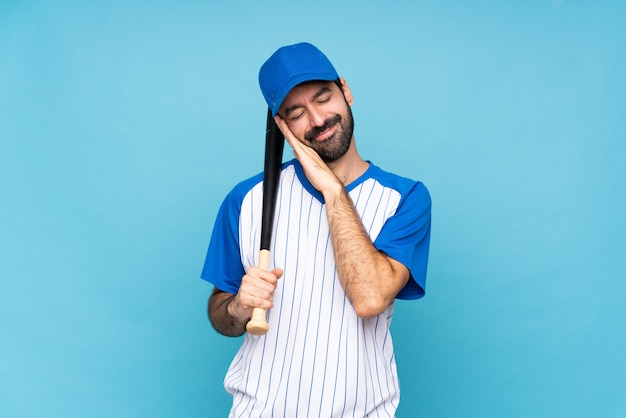 Young man playing baseball over isolated blue background making sleep gesture in dorable expression