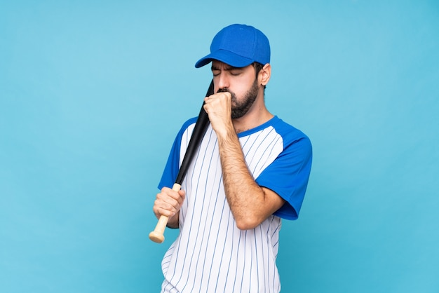Young man playing baseball over isolated blue wall is suffering with cough and feeling bad