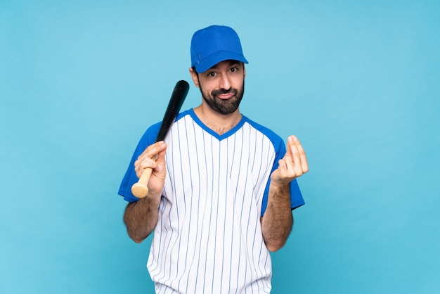 Young man playing baseball over isolated blue wall making money gesture