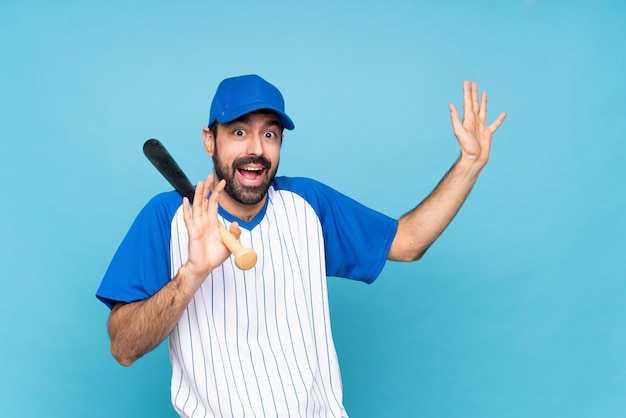 Young man playing baseball over isolated blue wall nervous and scared
