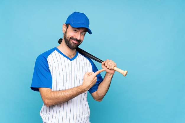Young man playing baseball over isolated blue wall pointing to the side to present a product