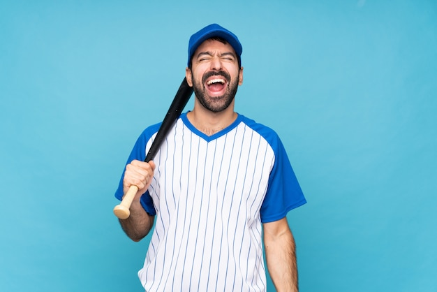 Young man playing baseball over isolated blue wall shouting to the front with mouth wide open