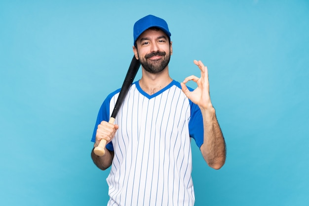 Young man playing baseball over isolated blue wall showing ok sign with fingers