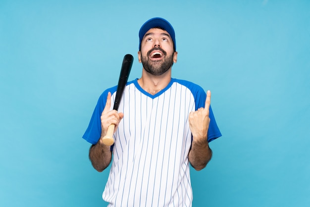 Young man playing baseball over isolated blue wall surprised and pointing up
