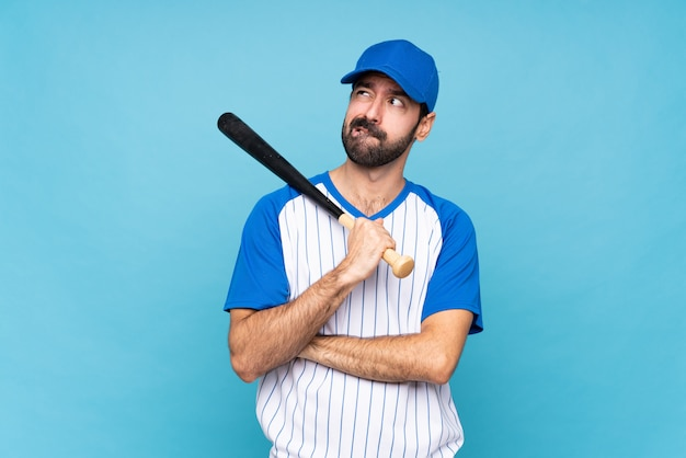 Young man playing baseball over isolated blue wall with confuse face expression