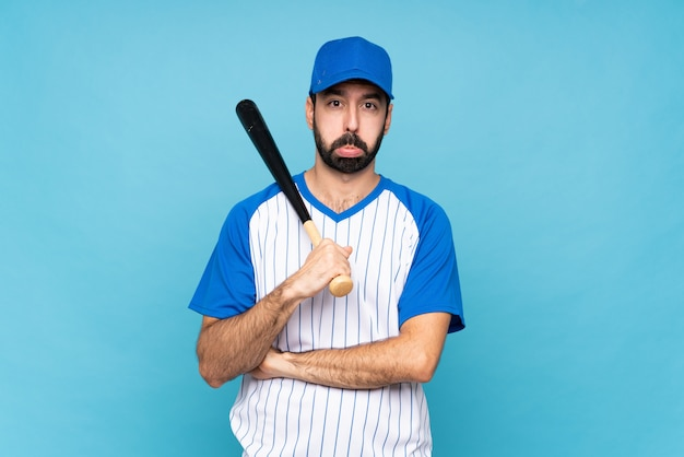 Young man playing baseball over isolated blue wall with sad and depressed expression