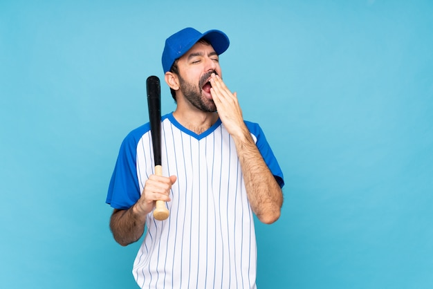 Young man playing baseball over isolated blue wall yawning and covering wide open mouth with hand