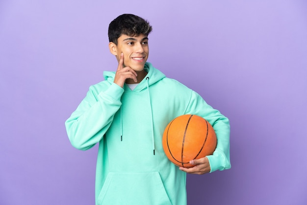 Young man playing basketball on isolated purple thinking an idea while looking up
