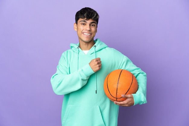 Young man playing basketball over isolated purple wall celebrating a victory