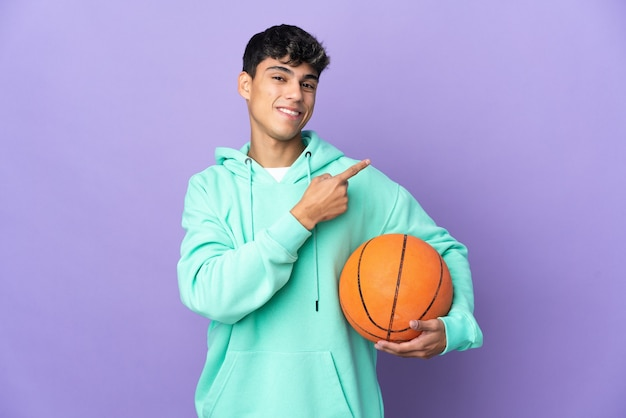 Young man playing basketball over isolated purple wall pointing to the side to present a product