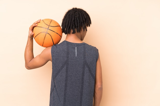 Young man playing basketball over isolated wall