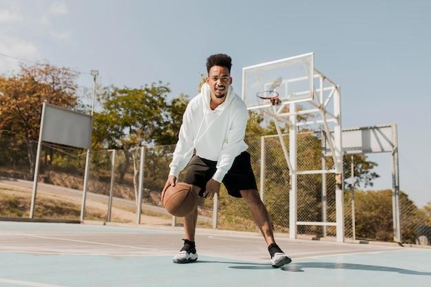 フィールドでバスケットボールをしている若い男
